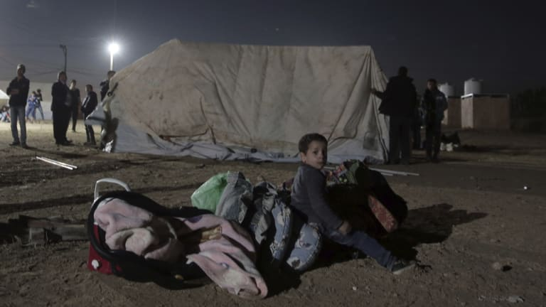 A Palestinian boy sits over his family's belongings next to tents set up near the Gaza Strip border with Israel.