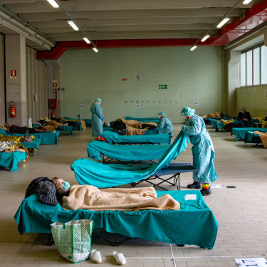 Medical personnel in Brescia, northern Italy, care for patients in an emergency temporary room set up to ease pressure on the country's healthcare system.