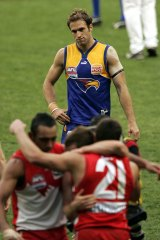 A dejected Chris Judd looks on as Sydney celebrates the 2005 grand final victory over West Coast.