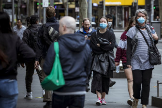 Melburnians wearing face masks in the city on Sunday.