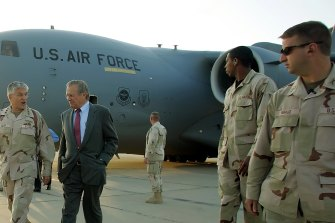 Donald Rumsfeld, second from left, arrives at Baghdad International Airport in April 2006.