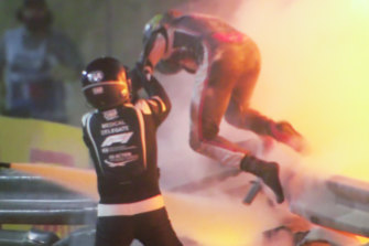 Romain Grosjean is helped from his burning car by marshals.
