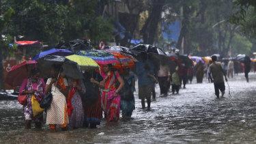 People wade through a waterlogged street during monsoon rains in Mumbai on Monday.