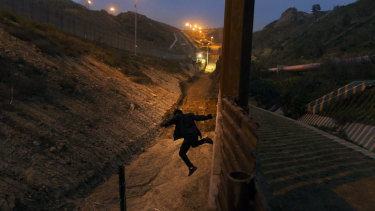 A Honduran youth jumps from the US border fence in Tijuana, Mexico, before Christmas.