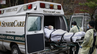 A patient is loaded into an ambulance by emergency medical workers outside a health centre in Brooklyn.