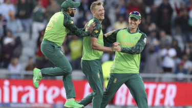 South Africa's Chris Morris, center, celebrates with teammates Dwaine Pretorius, right, and Tabraiz Shamsi after dismissing Australia's Alex Carey during the Cricket World Cup match.