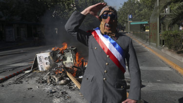 An anti-government demonstrator disguised as late military dictator General Augusto Pinochet salutes in Santiago on Wednesday.