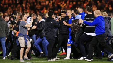 Boilover: The crowd invades the pitch after Colchester sealed the victory.