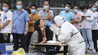 Workers line up for a test at a large factory in Wuhan.