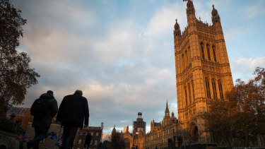 Pedestrians pass by the Houses of Parliament in London, on Wednesday.