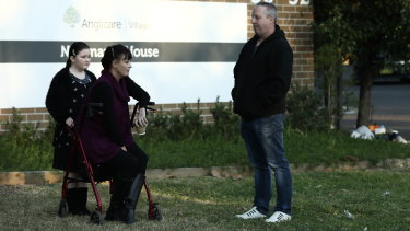 Relatives of residents Liz Lane with her daughter Samantha and Anthony Bowe gather outside Newmarch House on Tuesday.