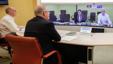 Secretary of the Department of Prime Minister and Cabinet, Phil Gaetjens and Australian Prime Minister Scott Morrison speak with NSW Premier Gladys Berejiklian (on screen) to discuss COVID-19 at Parliament House in Canberra on Sunday 22 March 2020.