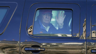 US President Donald Trump waves to supporters from his motorcade as people gather for a march in Washington.