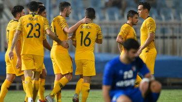Cruise control: Australia's Apostolos Giannou (with hand on neck of Aziz Behich) celebrates after scoring against Kuwait.