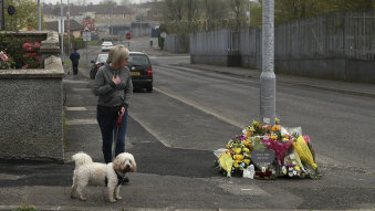Uneasy calm: A woman stops by a tribute for journalist Lyra McKee in Londonderry.