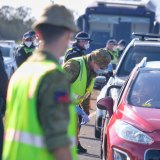 Members of the Australian Defence Force and Victoria Police at a vehicle checkpoint along the Princes Freeway near Little River.