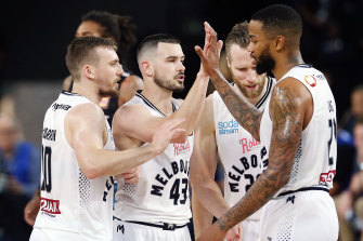 Coach wants more: Melbourne United teammates celebrate following a win over the Breakers.