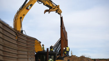 Workers replace sections of the existing border wall in Tijuana, Mexico.