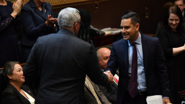 Independent MP Alex Greenwich shakes hands with Health Minister Brad Hazzard in the NSW Legislative Assembly after introducing the bill to decriminalise abortion.