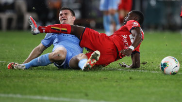 Melbourne City's Curtis Good and United's Pacifique Niyongabire collide.