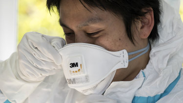 A staff member wears an N95 mask.
