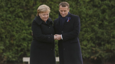 French President Emmanuel Macron and German Chancellor Angela Merkel hold hands after braving the rain to unveil a plaque in the Clairiere of Rethondes.