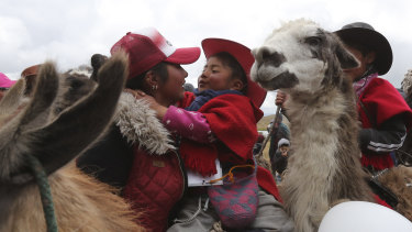 A mother embraces her child after he raced his llama at the Llanganates National Park in Ecuador.