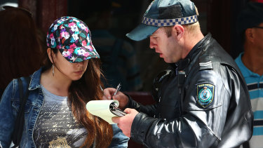 A pedestrian gets a fine for crossing the street on a red pedestrian light during a recent crackdown in Sydney.