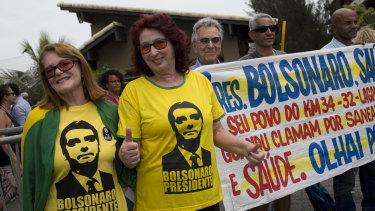 Supporters of President-elect Jair Bolsonaro wear T-shirts with his image, outside Bolsonaro's home where he was holding meetings in Rio de Janeiro on Thursday.