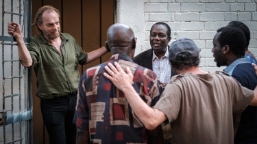 Playing a war photographer, Hugo Weaving listens to an African choir featuring a South Sudanese refugee played by Andrew Luri (facing camera) in Hearts and Bones.