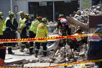 Emergency services workers at the site of the collapse.