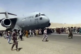 Hundreds of people run alongside a US Air Force C-17 transport plane at Kabul airport on Monday.