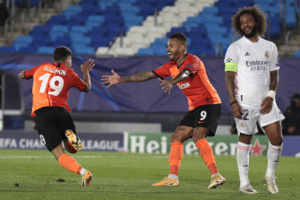 Shakhtar's Manor Solomon celebrates after scoring his side's third goal as Madrid's Marcelo Vieira looks on.