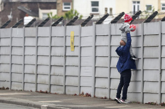 A man helps a child look over the fence at Liverpool's training ground, Melwood. EPL clubs have returned to training after the coronavirus shutdown.
