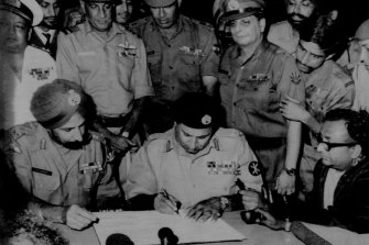 Lt. General A.A. K. Niazi (right) Pakistani (Seated second from left), signing the surrender document here today as Lt. General J.S. Aurora (left) Chief of India's eastern command, looks on. Other Pakistan and Indian army officers look on. December 16, 1971.