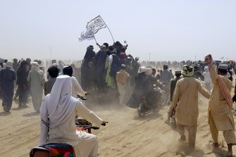Supporters of the Taliban carry the Taliban's signature white flags in the Afghan-Pakistan border town of Chaman on Wednesday.
