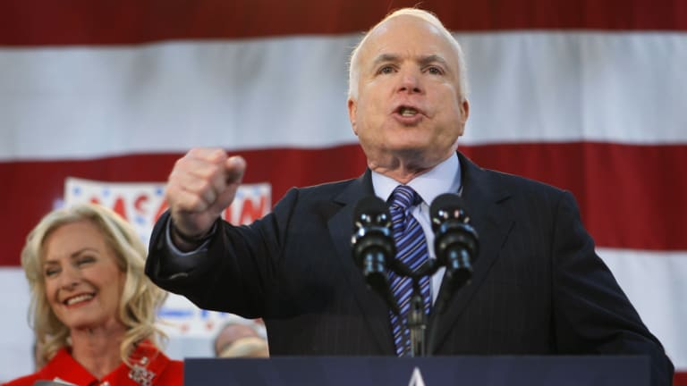 Republican presidential candidate Senator John McCain, standing with his wife Cindy, encourages his supporters to stand up and fight for America at the close of his address during a campaign rally in 2008.