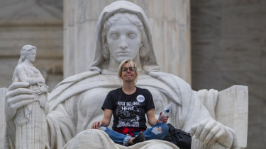Jessica Campbell-Swanson, an activist from Denver, sits in the lap of a sculpture known as the Statue of Contemplation of Justice on the steps of the Supreme Court Building where she and others protested the confirmation of Brett Kavanaugh as the high court's newest justice, in Washington, on Saturday.