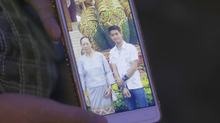 The aunt of coach Ekapol Chanthawong shows a picture of the coach and his grandmother on a mobile phone screen.