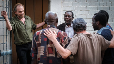 A war photographer played by Hugo Weaving listens to an African choir in Hearts and Bones.