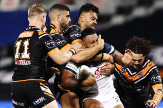 Francis Molo of the Cowboys is tackled by the Tigers defence.