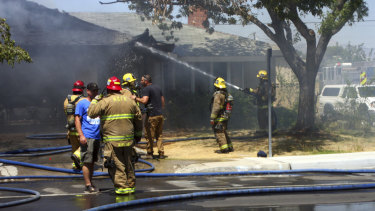 Kern County firefighters work to knock down a fire that severely damaged a home in Ridgecrest.