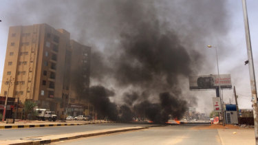 Burning tires set by protesters produce black smoke on road 60, near Khartoum's army headquarters, in Khartoum, Sudan, Monday.