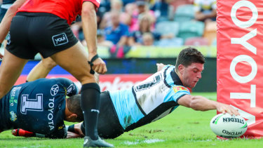 Stretch: Chad Townsend reaches out to open the try-scoring for the Sharks in Townsville.