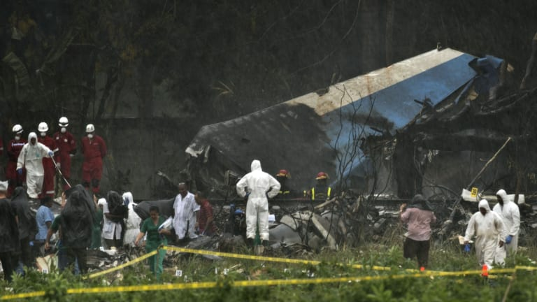 Rescue teams search through the wreckage site of a Boeing 737 that plummeted into a cassava field with more than 100 passengers on board, in Havana, Cuba.