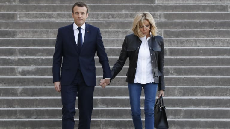 French President Emmanuel Macron, left, with his wife Brigitte Macron arrive to attend an interview with BFM television.