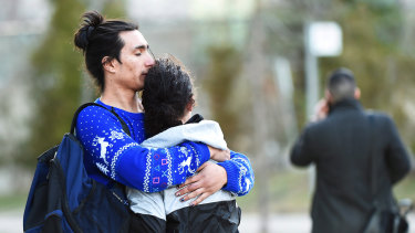 Two people comfort each other after a rented van plowed down a crowded sidewalk, killing multiple people in Toronto.