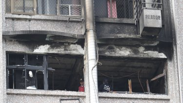 Fire inspectors view damages after a fire broke out at the Taipei Hospital in Hsinchuang, New Taipei City, Taiwan, on Monday.
