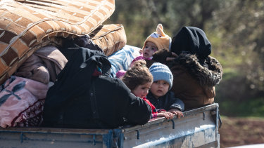 Displaced Syrian families ride in the back of a truck loaded with the family's possessions towards the Turkish border on Thursday.