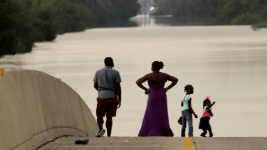 A family surveys floodwaters in Houston in the aftermath of Hurricane Harvey in September 2017, in Houston.